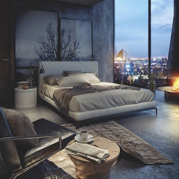 brown bed in large bedroom loft overlooking the city with forest paintings on wall