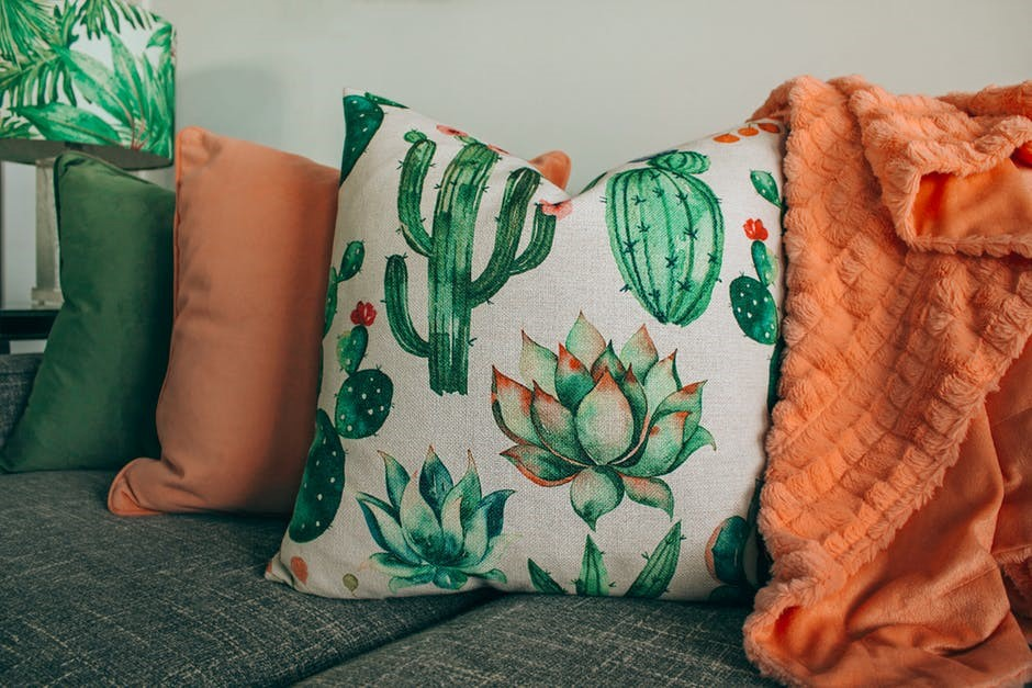 cactus pillow on couch with orange blanket and orange and green pillows on a neutral color grey couch
