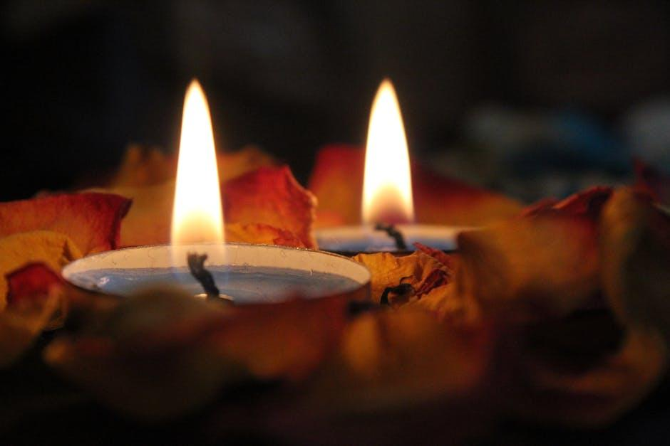 burning candles wrapped in fall leaves