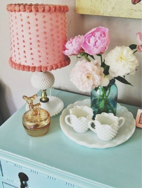 elegant teal night stand with pink fluffy lamp and blue vase with flowers