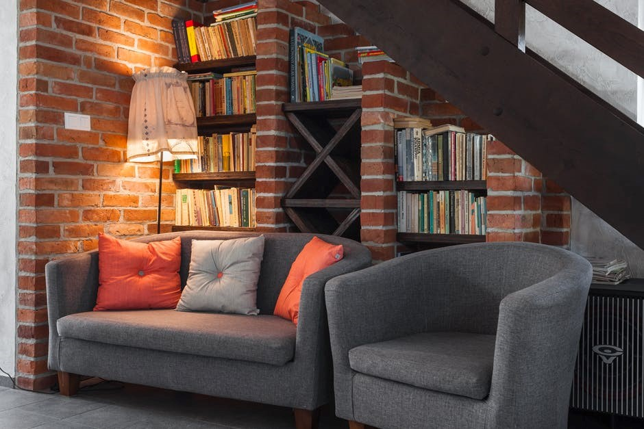 grey couches in a comfy reading nook under the stairs