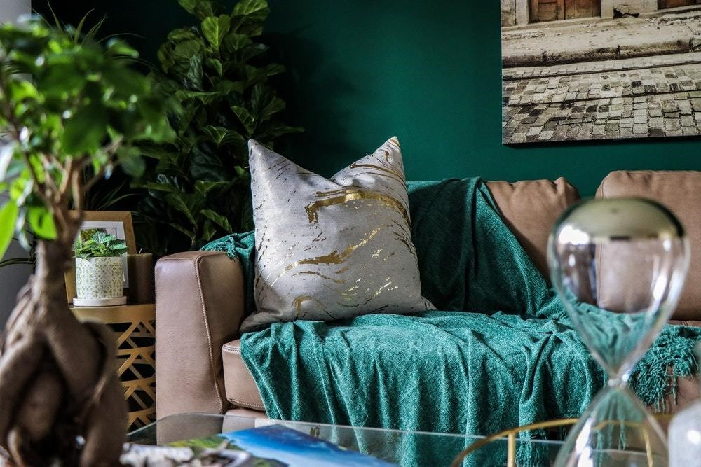 grey pillow with gold streaks on a grey couch with teal blanket