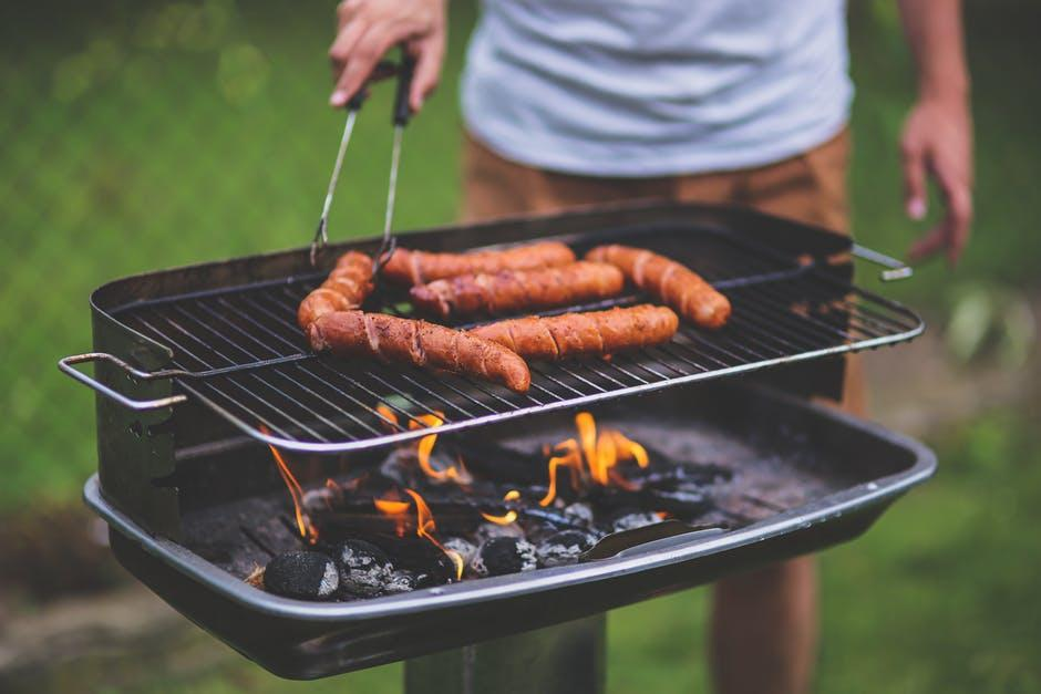 A man grilling hot dogs on a grill