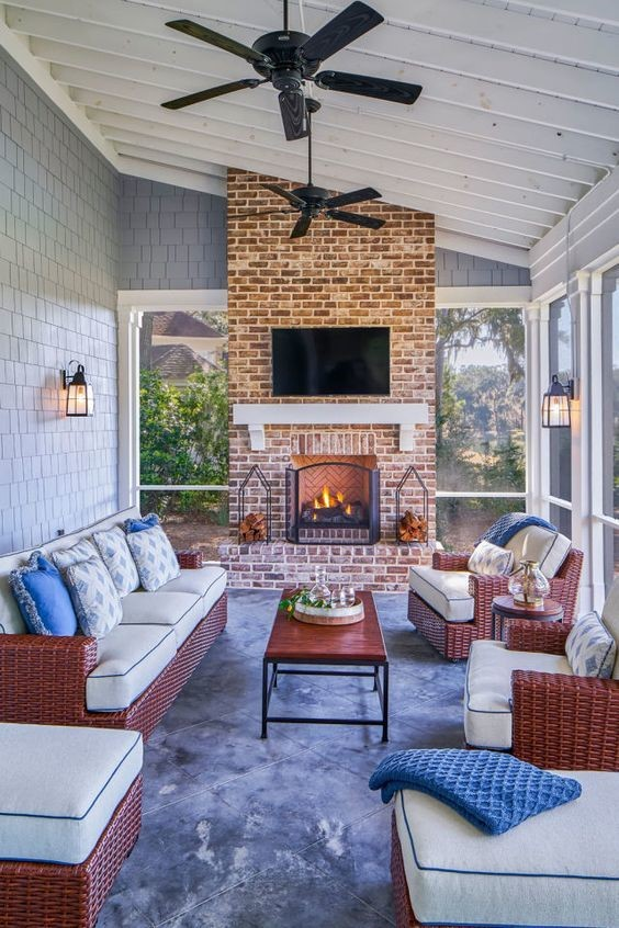 indoor outdoor sunroom with brick wall and flat screen