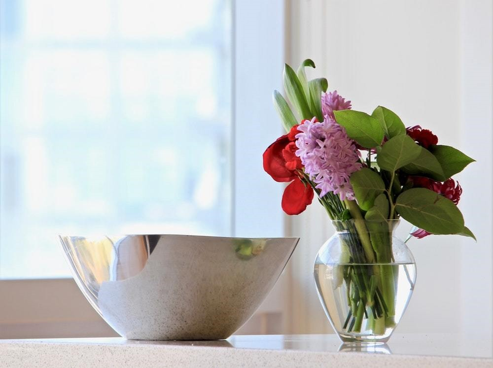 metallic bowl on countertop next to pretty flower vase with roses
