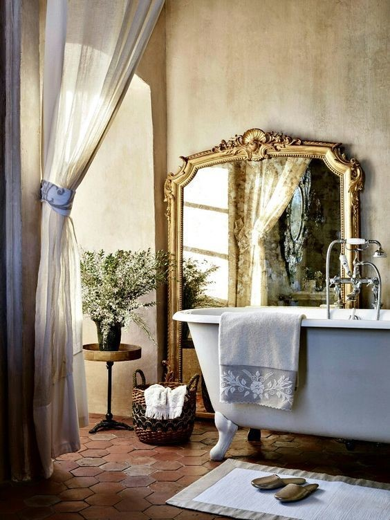 mirror on the wall in bathroom with claw tub bath