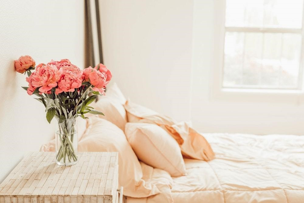pink flowers next to beige bedspread