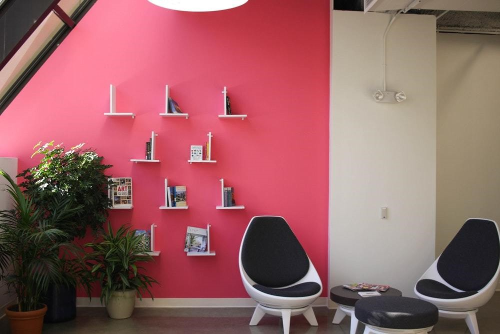 pink wall rom with blue and white modern chairs
