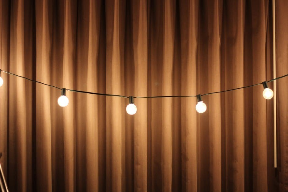 string lights against a brown curtain