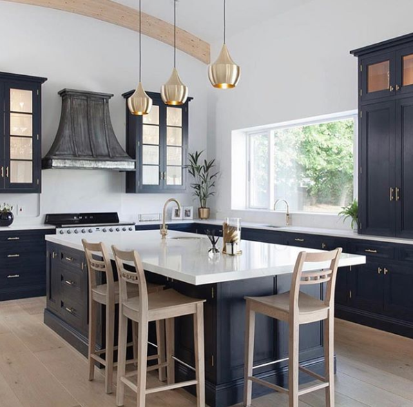 white kitchen island countertop on black island with gold pendants